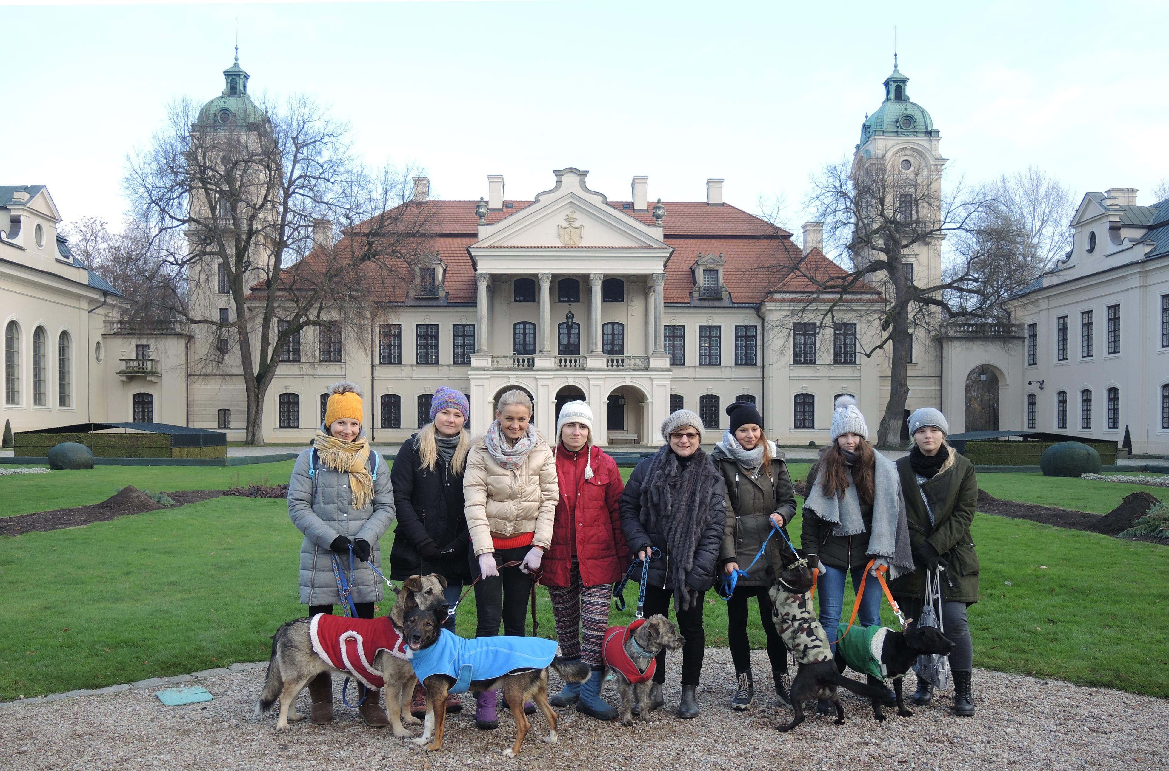 """Fotografia. Grupa ośmiu kobiet w różnym wieku, ubrana w zimowe kurtki i czapki stojąca na tle okazałej dwukondygnacyjnej rezydencji z portykiem i czerwonym dwuspadowym dachem oraz pobocznymi budynkami tworzącymi literę """"U"""". Pięć z nich trzyma psy na smyczy."""
