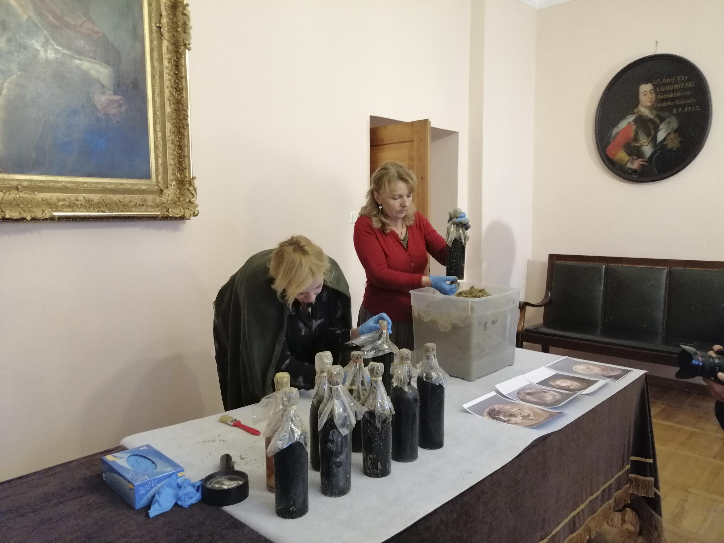 Fotografia. Dwie kobiety w lateksowych rękawiczkach. Jedna z nich nachyla się nad stołem i zabezpiecza szyjkę butelki z winem folią, druga wkłada zabezpieczone butelki do pojemnika wypełnionego piachem. Przed nimi osiem zabezpieczonych folią butelek z ciemnego szkła.