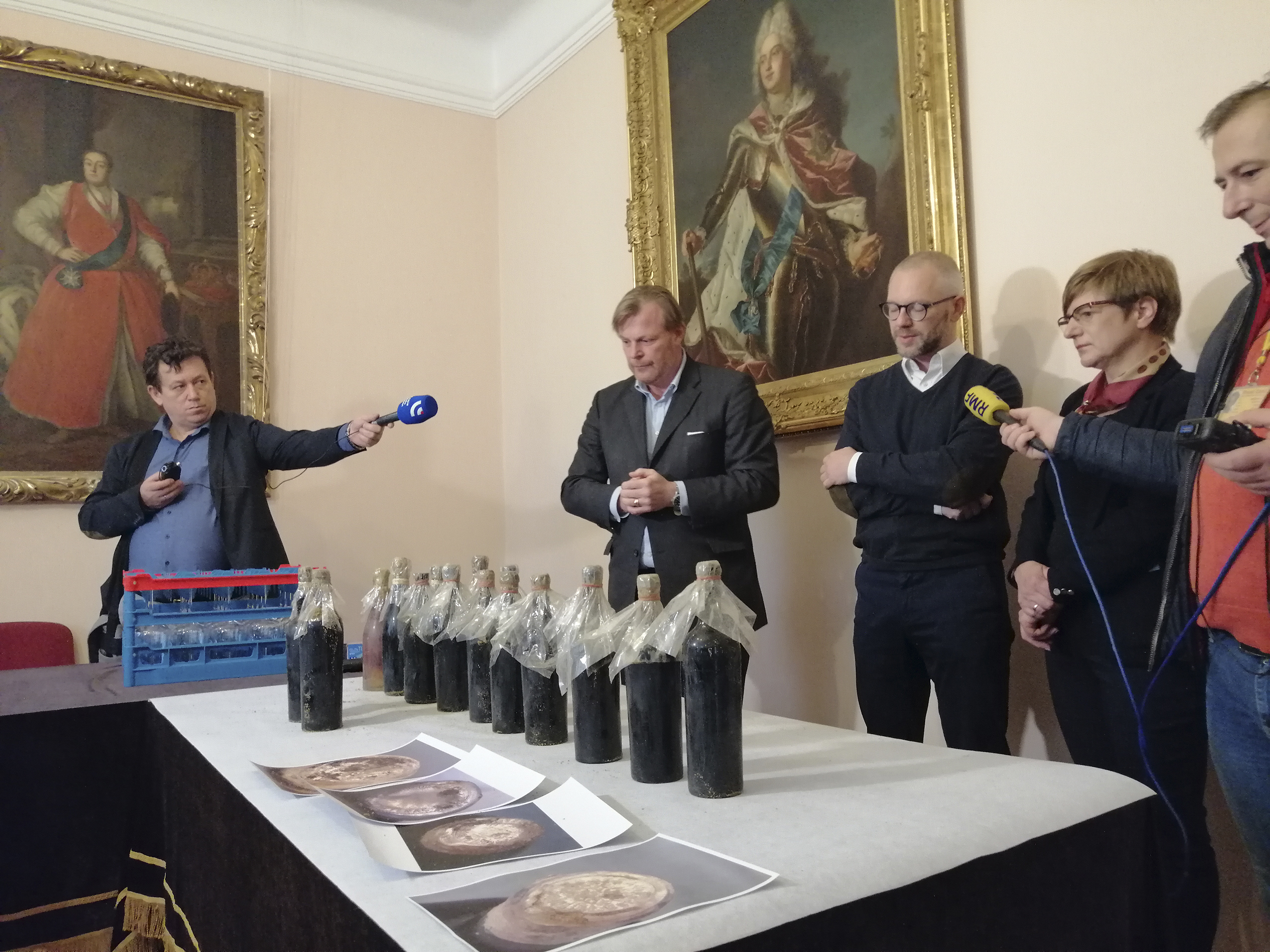 Fotografia. Konferencja prasowa. Dwóch dziennikarzy z mikrofonami skierowanymi w stronę rozmówców: kobiety i dwóch mężczyzn. Przed nimi na stole, ustawione w rzędzie zakurzone i zabezpieczone folią butelki do wina, jedenaście butelek z ciemnego szkła, jedna ze szkła jasnego.