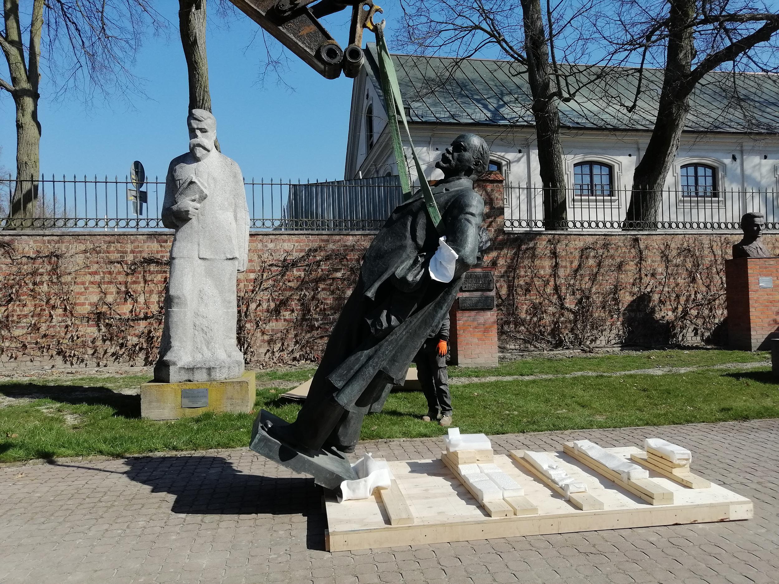 Fotografia. Pomnik Włodzimierza Lenina, postać całościowa. Rzeźba z brązu o wymiarach 260 x 120 x 75 cm podnoszona na pasach holowniczych do pozycji pionowej.