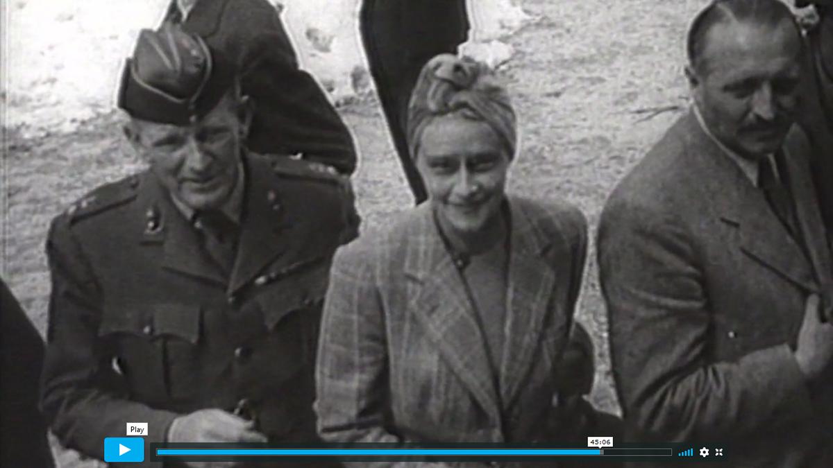"""Kadr z dokumentu fabularyzowanego """"Wir Geiseln der SS"""", (Jesteśmy zakładnikami SS). Dwóch mężczyzn i kobieta stojąca pomiędzy nimi. Mężczyzna po lewej stronie, w średnim wieku, ubrany w mundur, na głowie furażerka. Kobieta, młoda, ubrana w jasny żakiet w kratę, na głowie modnie upięty turban. Uśmiecha się. Mężczyzna po prawej stronie, ustawiony prawym profilem z głową skierowana en face. Ubrany w jasna marynarkę, modnie zaczesany, z wąsem."""