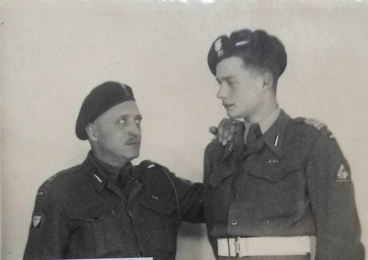 Czarno-biała fotografia. Dwaj mężczyźni ubrani w mundury, w beretach z orłem na głowie skierowani ku sobie, patrzą sobie w oczy. Starszy i niższy mężczyzna z wąsem opiera lewą rękę na ramieniu niższego stopniem i młodszego mężczyzny.