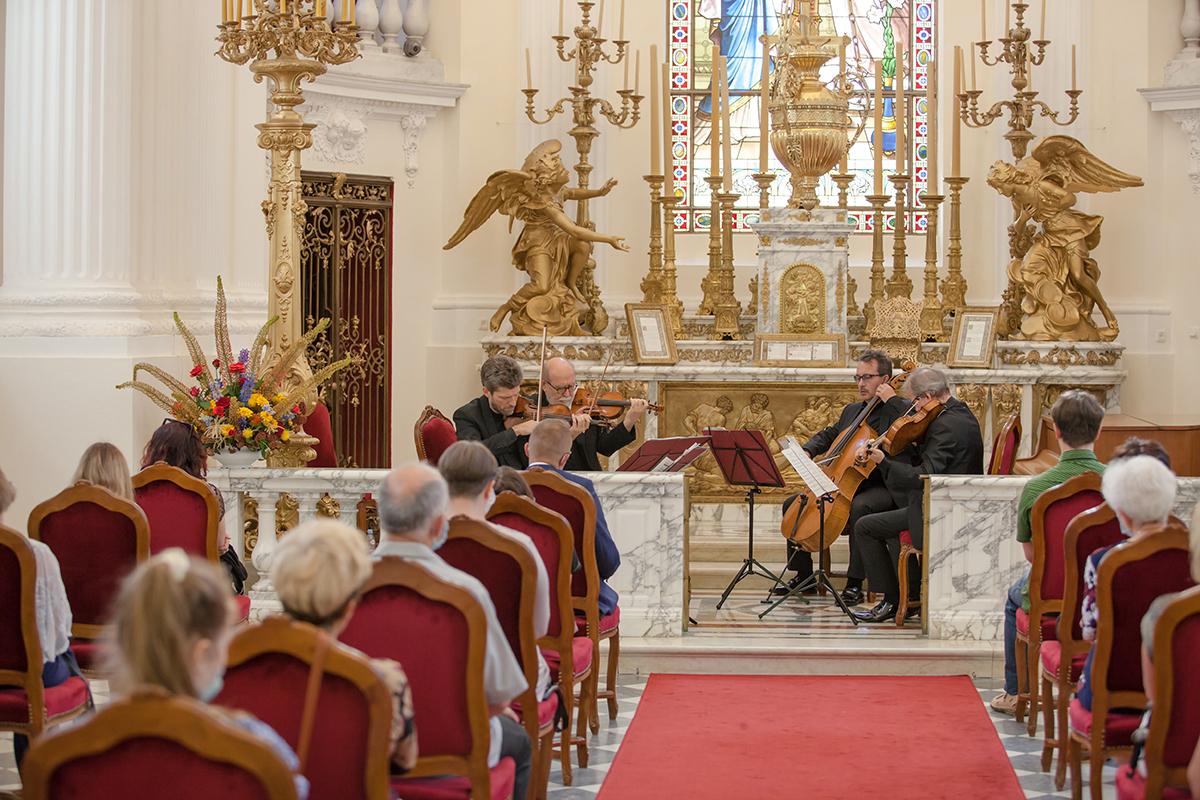 Widok od strony wejściowej na kaplicę. Przy ołtarzu czterej muzycy grający na instrumentach. Słuchacze siedzą na krzesłach ustawionych w dużej odległości od siebie.