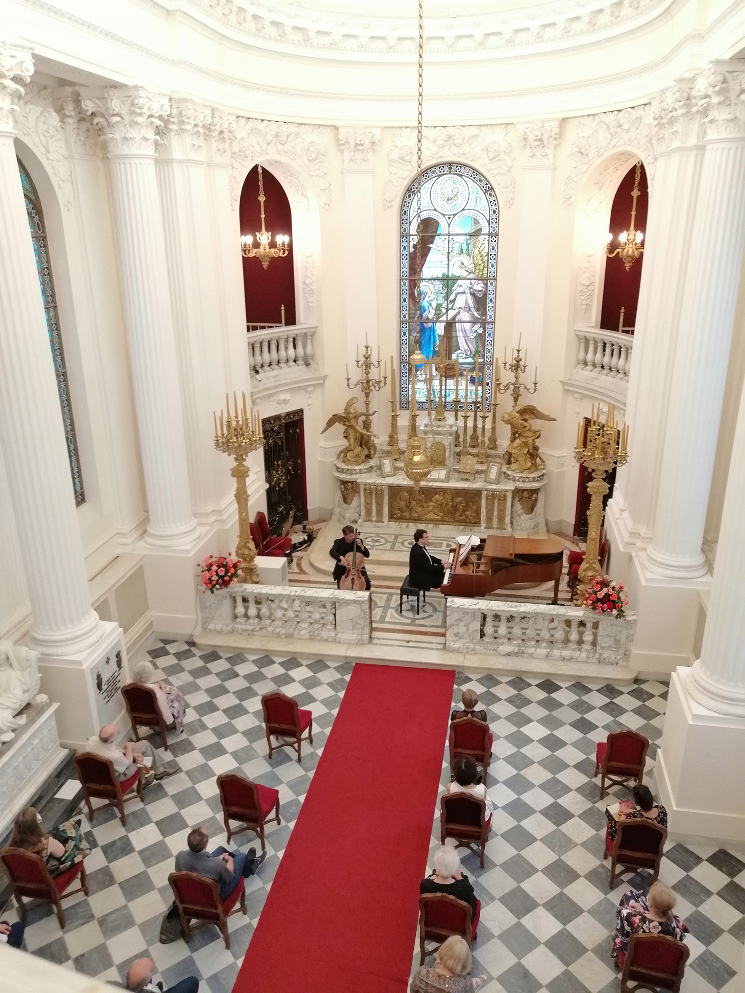 Fotografia z wysokości. Wnętrze jasnej kaplicy. W prezbiterium dwóch artystów. Po prawej stronie mężczyzna grający na fortepianie, po lewej stronie na wiolonczeli. W nawie głównej siedzący pojedynczo, w równych odległościach od siebie słuchacze.