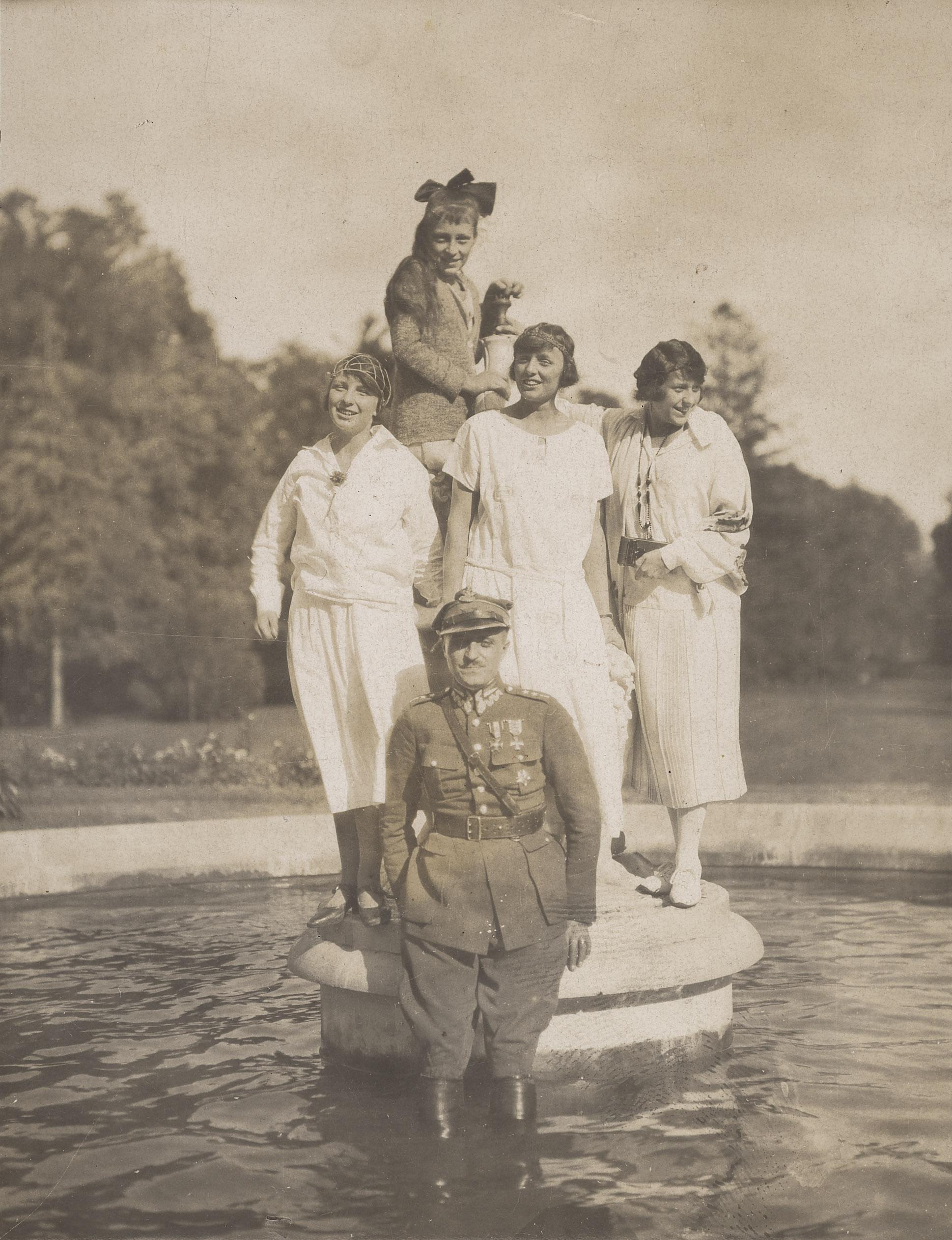 Czarno-biała fotografia. Aleksander Zamoyski z żoną Jadwigą i jej siostrami: Izabelą, Różą i Marią. Młodzi ludzie w fontannie. Na pierwszym planie mężczyzna ubrany w mundur stoi w wodzie po kolana. Za nim, stojące na cokole fontanny, trzy kobiety ubrane w jasne, proste sukienki z niskim stanem. Włosy krótkie, ozdobione delikatnymi dodatkami. Za nimi, stojąca najwyżej najmłodsza kobieta ubrana w sweter. W długie włosy wpięta na czubku głowy duża kokarda.