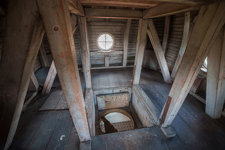 Fotografia pozioma. W centralnym kadrze znajduje się okrągłe okno ze szprosami, które przecinają się tworząc krzyż. Pod nim znajduje się parapet wykonany z drewna. Całość jest wkomponowana w drewnianą ścianę . Złożoną z poziomych desek i pionowych beli . Przed całą ścianą znajduje się podwyższenie przypominające scenę . Przy jej brzegu znajdują się pionowe drewniane słupy podtrzymujące konstrukcje stropu.