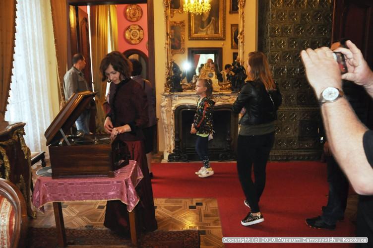 Fotografia. Kobieta ubrana w stylizowaną bordową suknię nastawia gramofon. W tle spacerujący po pomieszczeniu turyści.