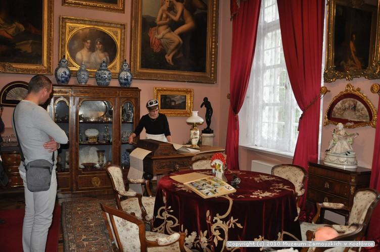 Fotografia. Przytulnie urządzone wnętrze, ściany pomalowane na jasnokawowy kolor zdobią obrazy w bogato rzeźbionych i złoconych ramach. Wyposażenie uzupełniają dziewiętnastowieczne meble. W głębi pokoju kobieta w stroju pokojówki nakręca korbką instrument muzyczny – pianomelodikon. Przygląda się jej zaciekawiony mężczyzna.