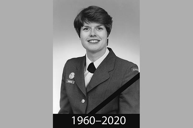Czarno-biała fotografia en face młodej kobiety ubranej w wojskowy, galowy mundur. Włosy ciemne, krótko obcięte, oczy ciemne, uśmiecha się szeroko. Poniżej napis: 1960-2020.