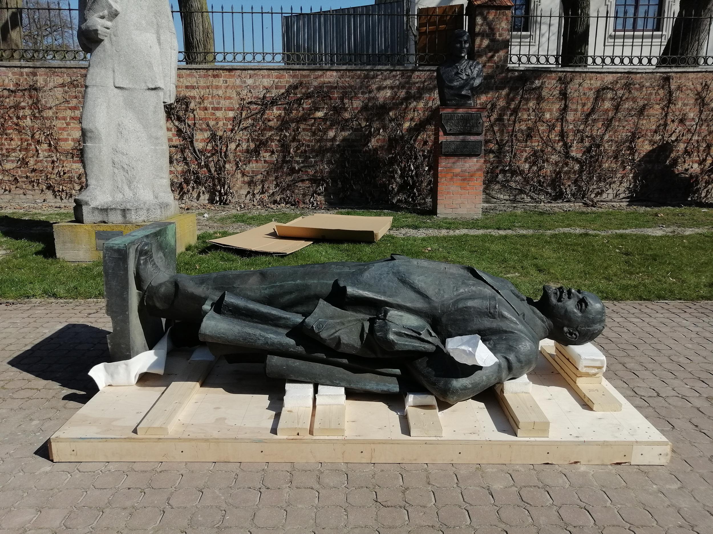 Pomnik Włodzimierza Lenina, postać całościowa. Rzeźba z brązu o wymiarach 260 x 120 x 75 cm ułożona poziomo na drewnianej podstawie.