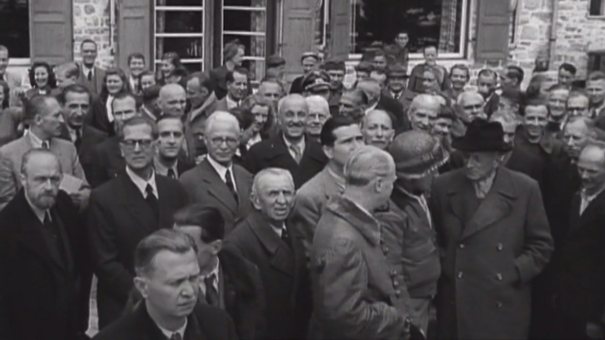 """Kadr z dokumentu fabularyzowanego """"Wir Geiseln der SS"""", (Jesteśmy zakładnikami SS).  Duża grupa ludzi na tle budynku z kamienną fasadą i okiennicami. Postacie z bliższego planu skierowane twarzą w stronę fotografa. Po prawej stronie u dołu trzech mężczyzn zajętych rozmową."""