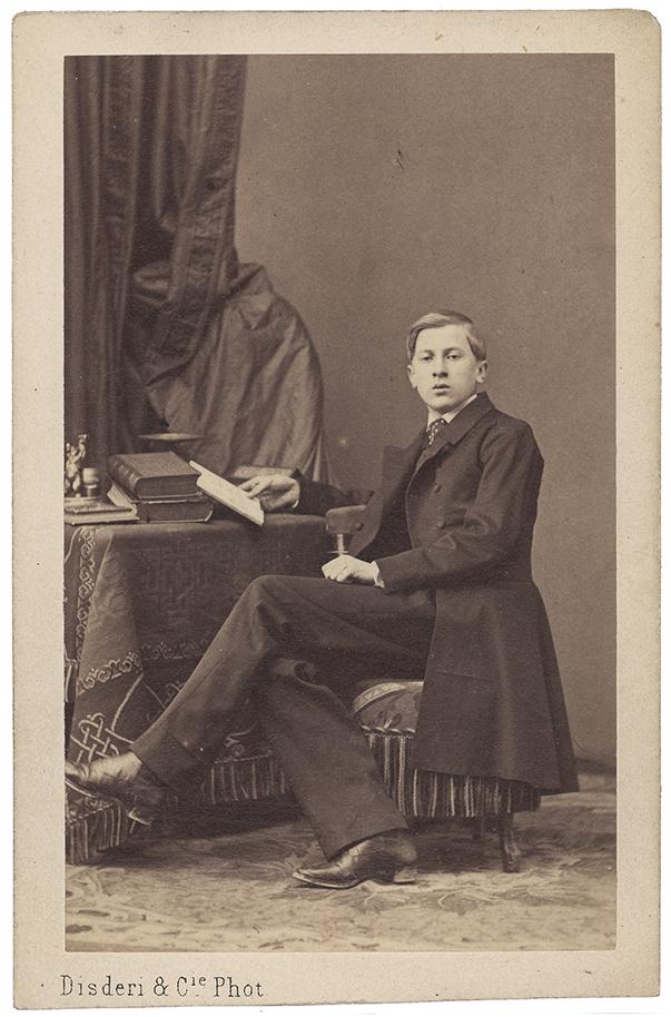 Fotografia zabytkowa, pionowa. Młodzieniec w całej postaci, siedzący przy stoliku, zwrócony w lewo, głowa en face; w tle z lewej kotara.