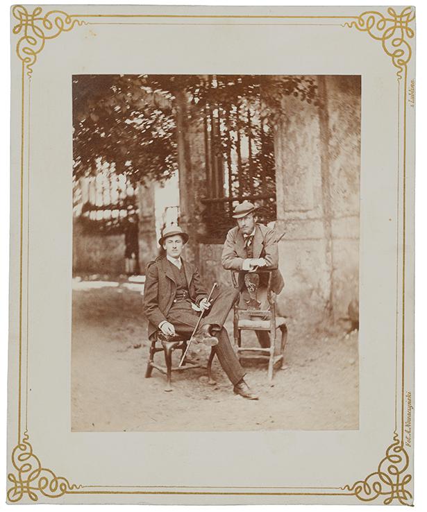 Fotografia zabytkowa, pionowa. Dwaj elegancko ubrani, młodzi mężczyźni przed bramą pałacową w Kozłówce. Mężczyzna po lewej stronie siedzi na krześle, z nogami skrzyżowanymi na wysokości kolan. W lewej ręce trzyma laseczkę. Mężczyzna po prawej ciężar ciała składa na oparcie krzesła podpierając się o nie ramionami.