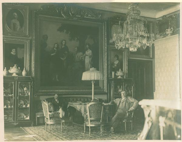 Wnętrze salonu wypełnionego obrazami w ozdobnych ramach i meblami. Na ścianie na wprost na środku duży obraz z czterema postaciami. Po jego obu stronach portrety. Pod dużym obrazem kanapa z siedzącym starszym mężczyzną, przed nią stół z wysoką lampą z białym abażurem, wokół stołu fotele, na jednym z nich siedzi Konstanty Zamoyski. Po obu stronach kanapy przeszklone szafki z porcelaną. W prawym roku biały piec kaflowy. Na podłodze wzorzysty dywan. Zdjęcie w kolorze sepii.
