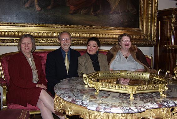 Fotografia. Cztery osoby, 3 kobiety i mężczyzna, ubrani elegancko, siedzą za stołem. Wszyscy uśmiechnięci.
