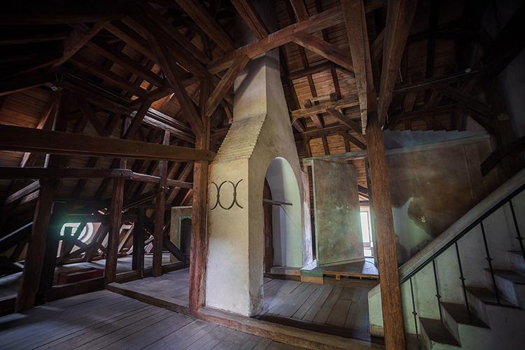 Fotografia pozioma. Na środku znajduje się połączenie dwóch kominów. Po ich prawej stronie jest murowana ozdobna balustrada, do której prowadzą proste schody. Konstrukcja więźby dachowej otacza obiekt. Na dole zdjęcia widać drewnianą podłogę.